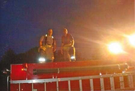 firefighters on top of a firetruck