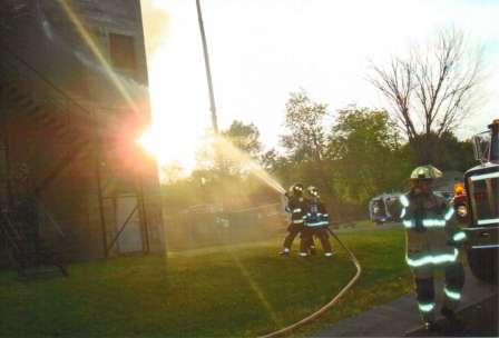 firefighters spraying a hose at a building